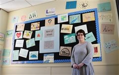 Latin teacher Stephanie Spaulding stands in front of one portion of the 'River of Words' art installation project, which was undertaken by World Language students across all three divisions.
