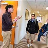 Teacher Alexander Kunst talking with students in the hallway at Severn School.