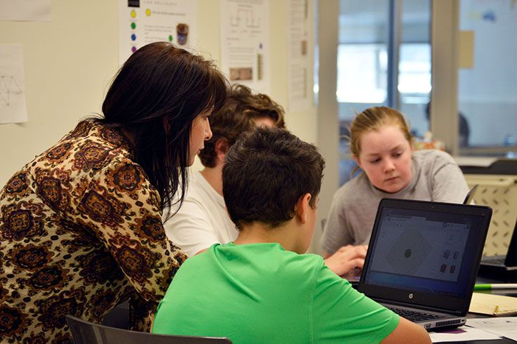 In the Graw Innovation center, Ms. Kelly Wilson helps students learn how to use Tinkercad to create 3D digital designs.