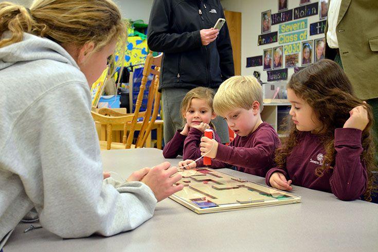 Severn School sixth graders show prekindergarten students how to use their custom made educational games.