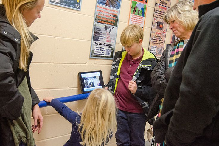 """Severn students and family gather around the iPad to look at digital designs."""" width="""