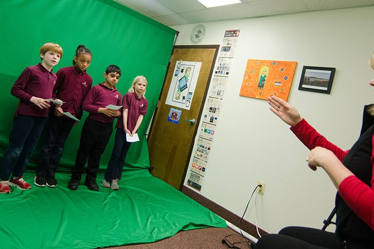 Severn School students presenting in front of a green screen.