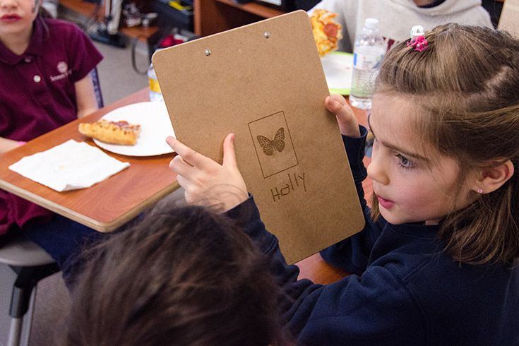 Severn School elementary school student holds a clipboard with her name on it.