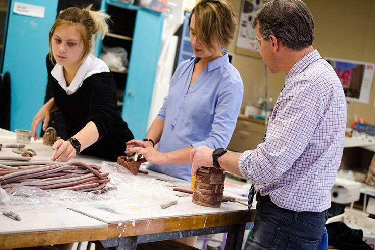 Severn School teachers work with a ceramics student to make coil pots.