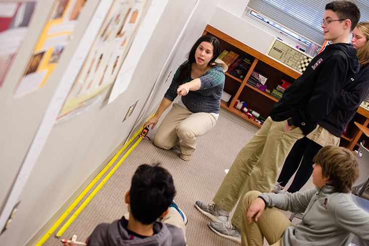 Severn School teacher helps students set up tape measures for a math project.
