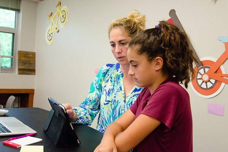 Severn School student looks at iPad with student.