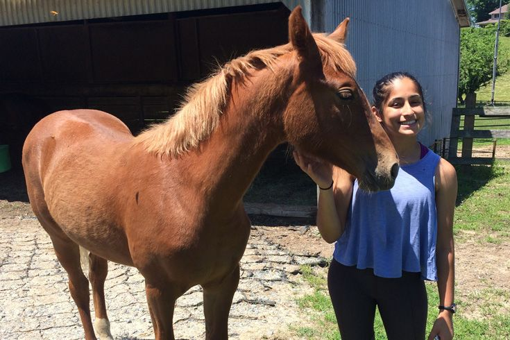 Severn School student poses with a horse.