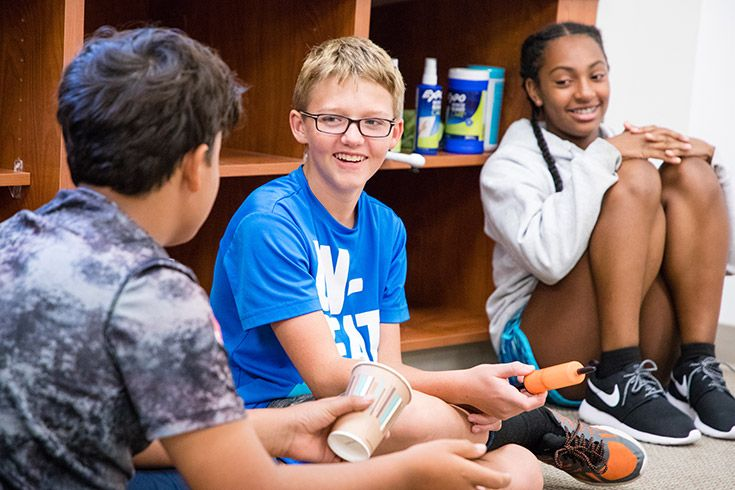 Severn School middle school students talk and smile together during an advisory activity.
