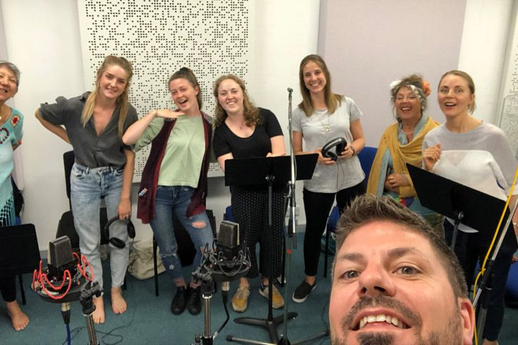 Teacher takes a selfie with a group of singers.