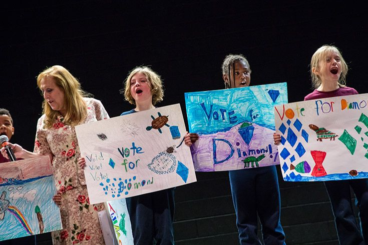 Severn School elementary school students present campaign posters on a stage.