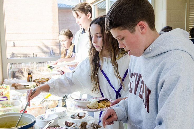 Severn school middle school students make plates of food at the Saturnalia buffet.