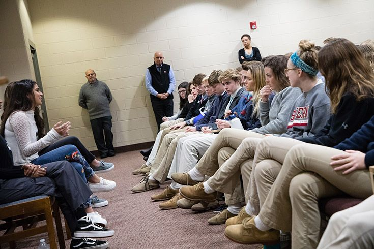 Severn School high school students sit at a panel in front of a group.