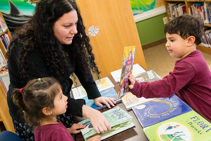 Severn School teacher looks at a book with two preschool students.