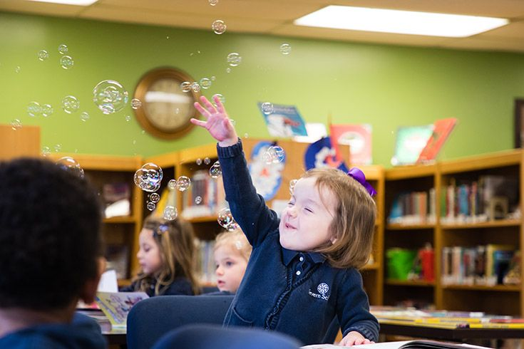 Severn School preschool student with bubbles in the library