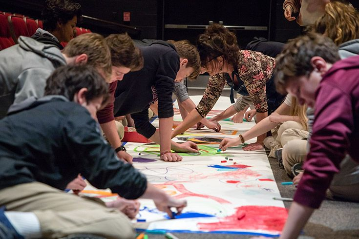 Severn School students drawing on a mural on the floor.