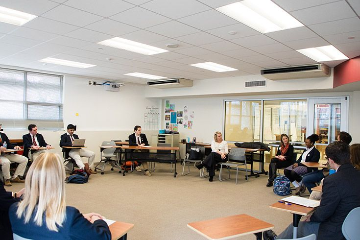 Students and teachers sit in a circle for a class discussion.