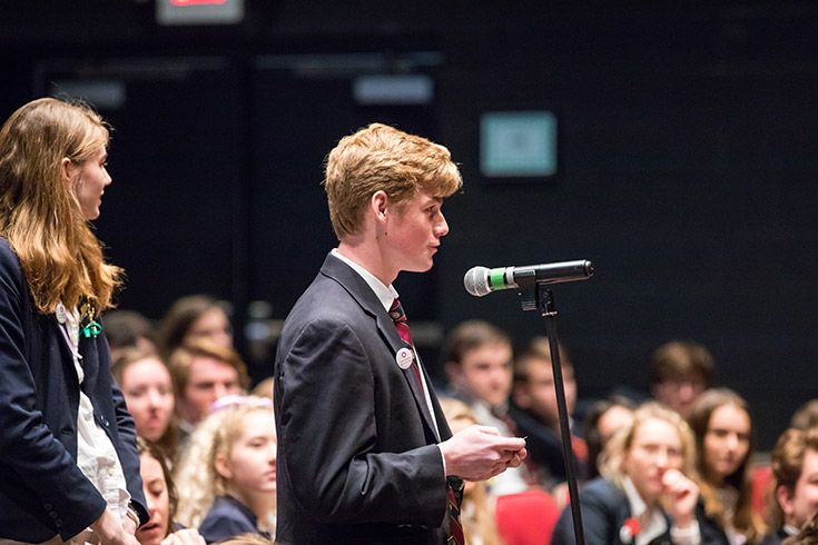 Severn School student stands at a microphone.