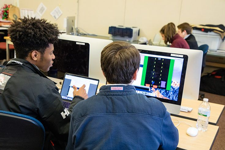 Two students programming on a computer.