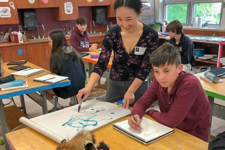Visiting artist shows Severn School Middle School student how to draw from a taxidermied animal model.