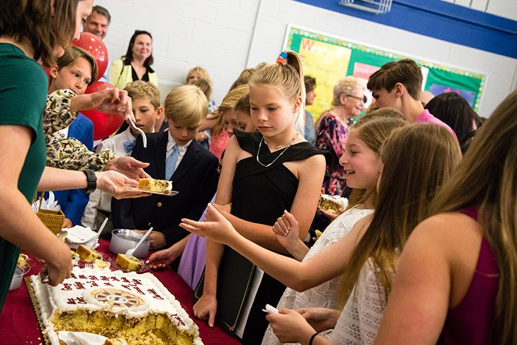 Severn School students get a slice of cake after the 5th grade promotion ceremony
