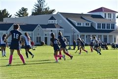 Girls Varsity Field Hockey players face an opponent.