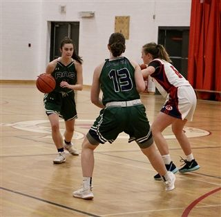 Sophie Milner (No. 13) sets a screen for Rothesay Netherwood School Riverhawks teammate Ally McLellan (with ball) against the Rothesay High Red Hawks. Photo: Courtesy of Kayla Blackmore