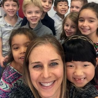 Teacher poses with elementary school students