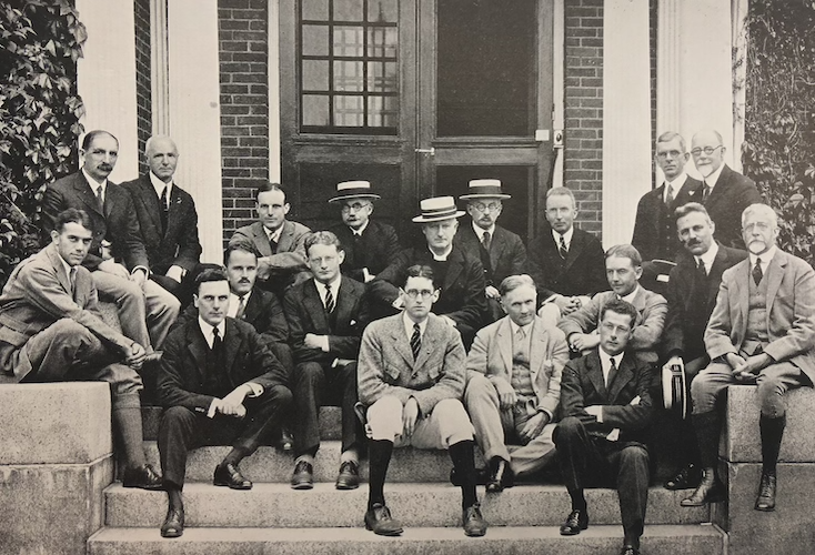 Groton School faculty sitting on the steps of the Schoolhouse, ca. 1920