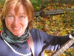 Yani Batteau with fall leaves and her guitar.