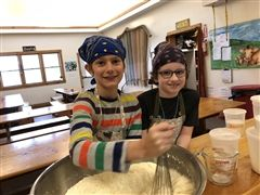 Students stir a mixture while working in the kitchen.