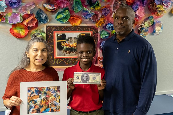 Justin Lane (center), whose artwork earned him a $1,000 prize, is joined by Visual Arts Instructor Nina Silverman-Weeks and his father Jack after receiving his award. Justin's efforts also resulted in the Visual Arts Department receiving art supplies valued at $1,500