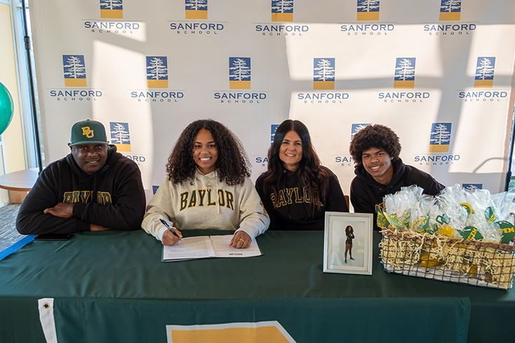 Zöe Collins '20 (second from left), surrounded by her family, signs her National Letter of Intent to participate in Baylor University's Acro and Tumbling program. Photo courtesy of Kevin McDermott.