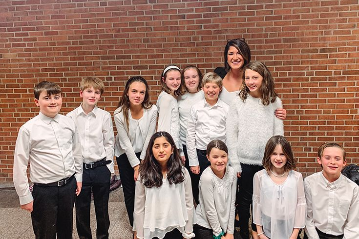 Sanford Performing Arts Instructor Jenn Kelman (standing, 2nd from right) joins members of Sanford's Fifth- and Sixth-Grade Chorus following the Holiday Spectacular at John Dickinson High School.