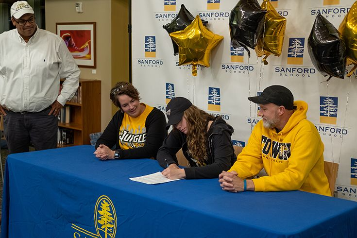 Allie Kubek '20—joined by her parents and Sanford Girls' Basketball Coach Marcus Thompson—signs a National Letter of Intent to play basketball at Towson University.