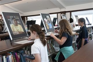 "Lower Schoolers study photos and stories from ""The Road to Freedom: Portraits of People with Disabilities."""