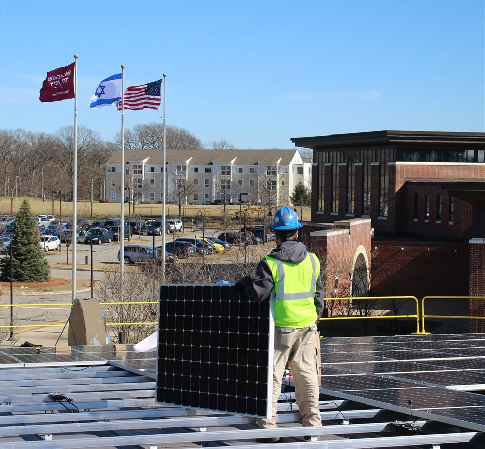 Workers installing the more than 800 solar panels on the Gann Academy SAC roof.
