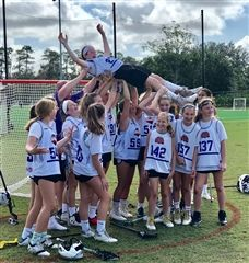 The lacrosse team laughs as they hold goalie Millicent Critchfield up after their tournament.