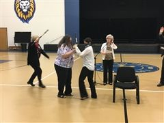 Mrs. Hudler, the traveller, is attacked by two robbers, Mrs. Thomas and Mrs. Monsalve.