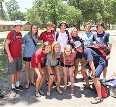 Fisher (pictured center in the white t-shirt) serving with his friends at Camp Blessing.