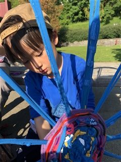 Student weaving a large dream catcher