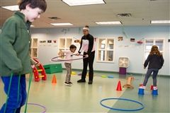 Middle School students set up an obstacle course for children in the Voyagers Room during indoor play.