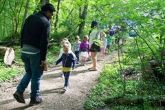 Discovery Room children explore Rock Creek Park to gather supplies for an art project with Mario.