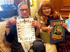 A student sits with Justice Ruth Bader Ginsburg. Both people are holding books.