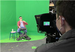 A student films an actor performing in front of a green screen.