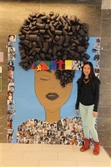 Muralist Elizabeth Ji '21 poses with her piece featuring accomplished men and women of color. The piece is on display in The Hun Middle School.