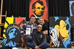 Mete Eser '14 and Courtney Caldwell '14 posed with Erik Wahl in front of the artwork he created during his two presentations at The Hun School of Princeton.