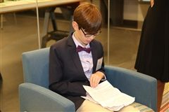 Sixth grader Ben Novik '24 looks over his speech at the Red and Black Dinner