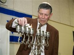 Dr. Michael Och lights the hanukkiah at the school's rededication as Golda Och Academy in December 2010.
