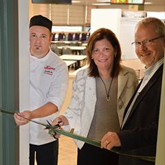 Head of School Joanne Kamins and representatives from Dana cut the ribbon to reopen our dining hall.