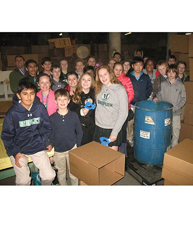 Middle School students pack boxes for the SHARE organization during a recent Service Friday.